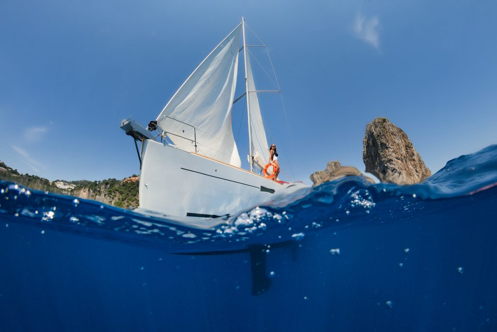 Woman on sailing yacht floating on the sea against the backgroun